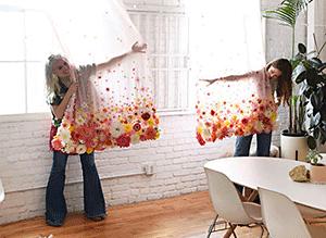Две девушки декораторы показывают шторы, которые они украсили цветами из шелка